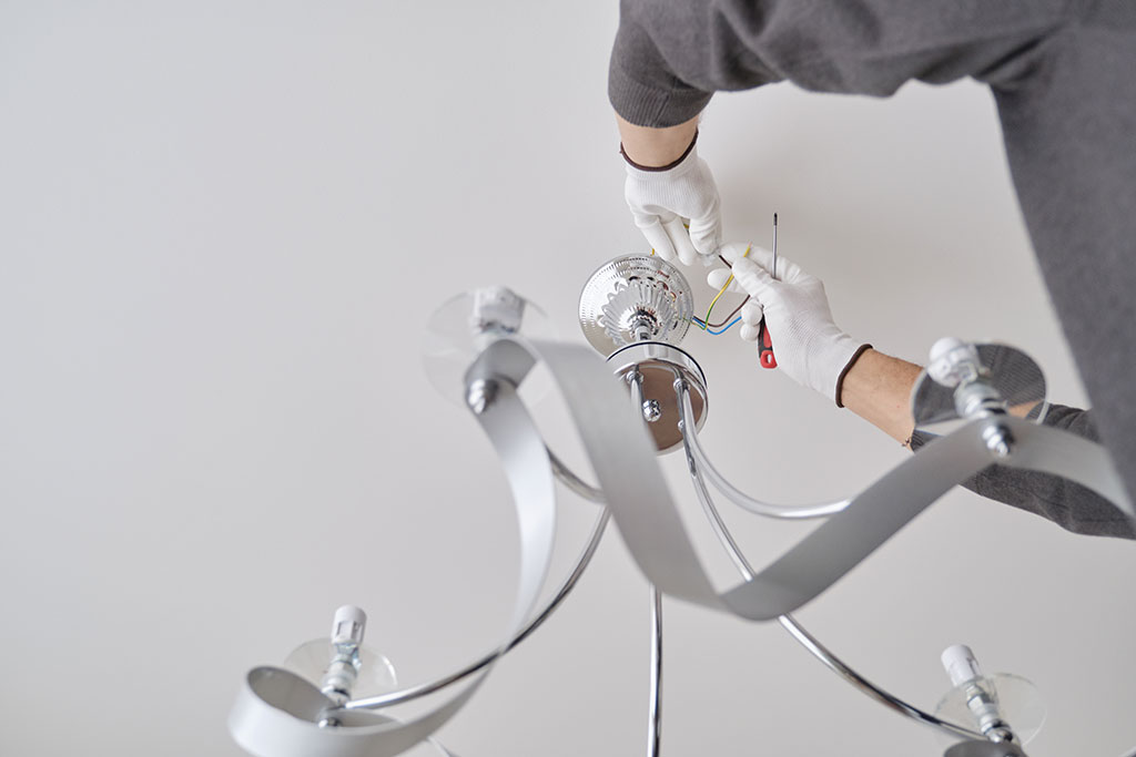 Installation ceiling lamp, hands of male electrician fixing chandelier with use of professional tools